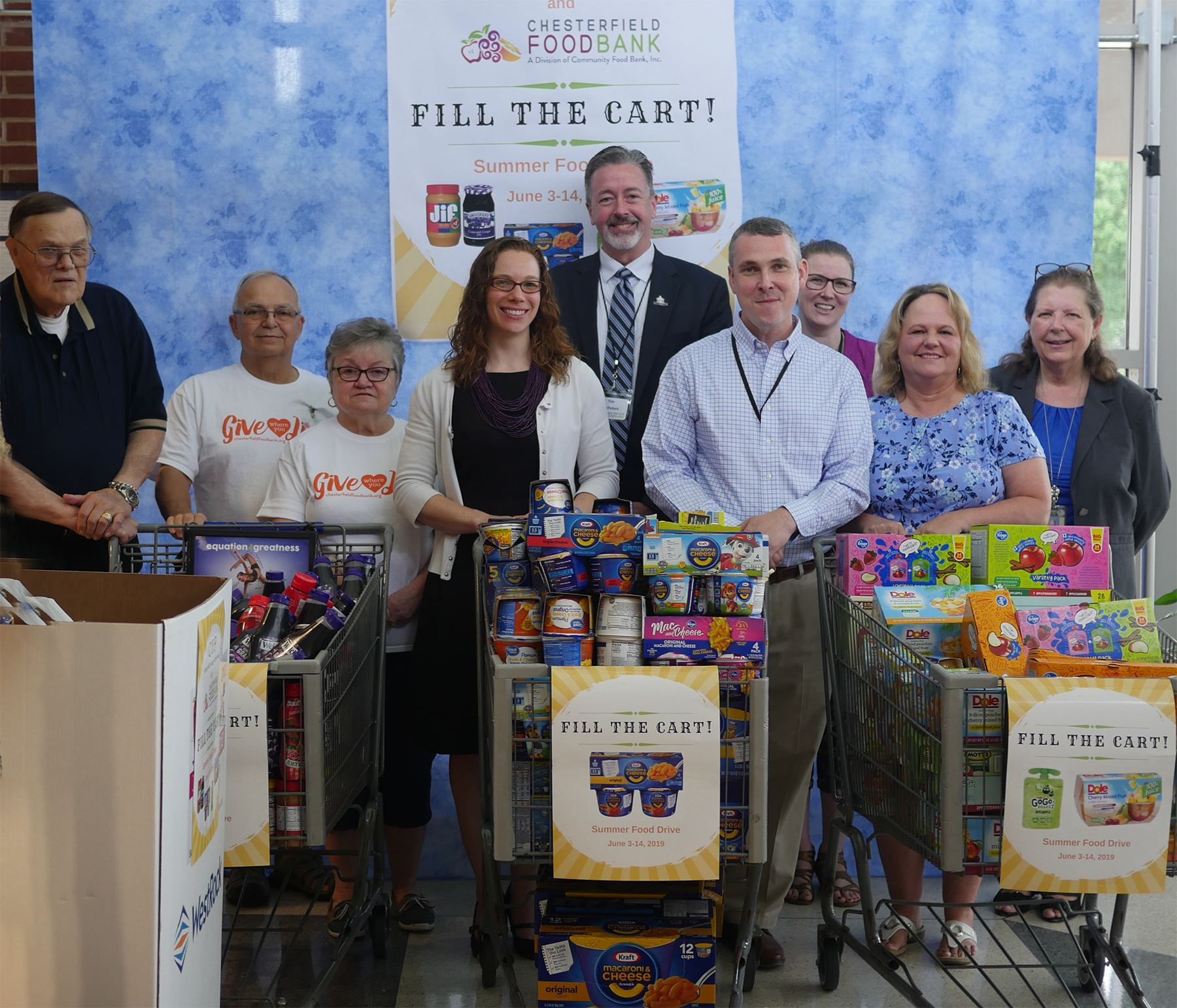Chesterfield employees with carts full of food collected during summer food drive
