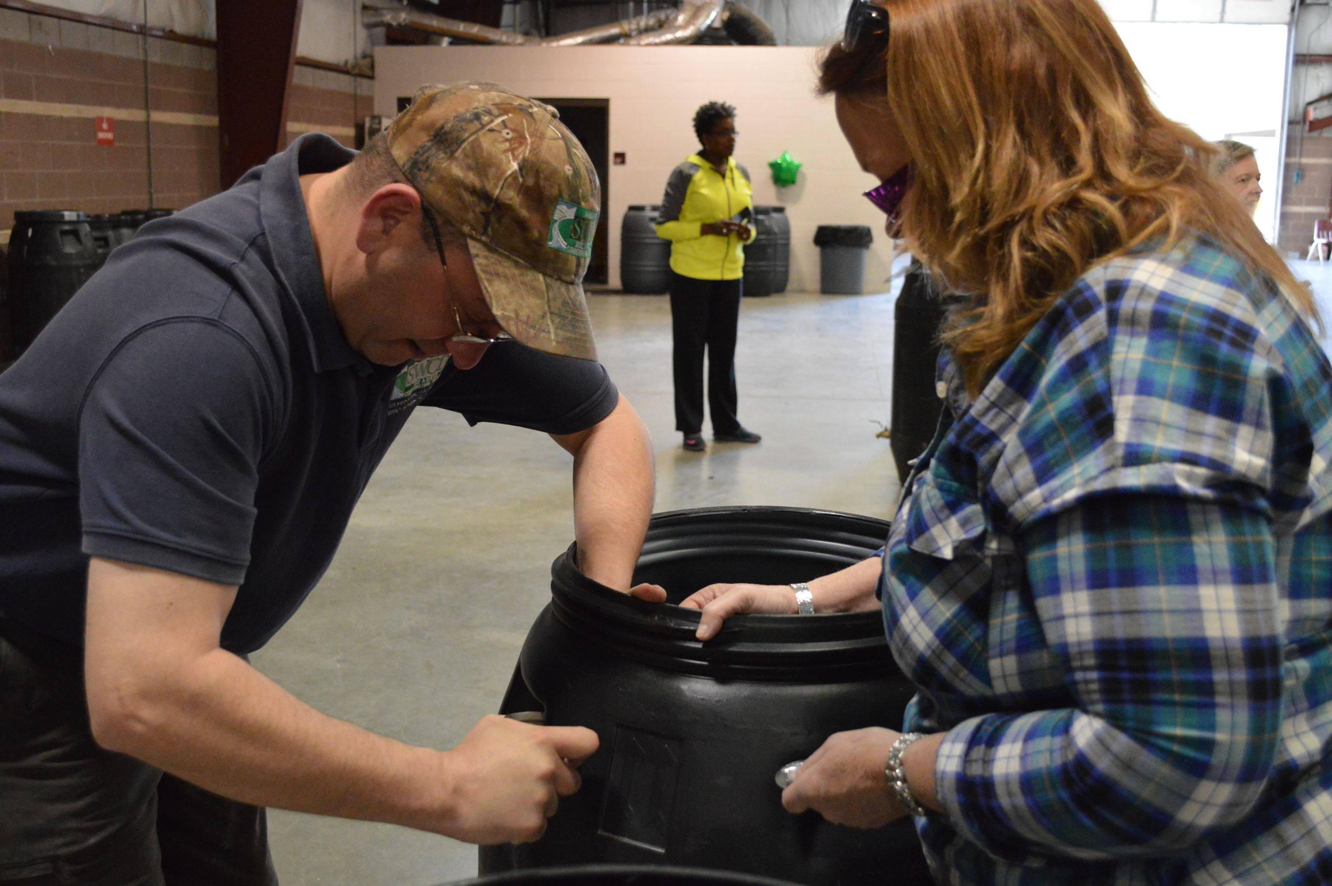 Man and woman building a rain barrel